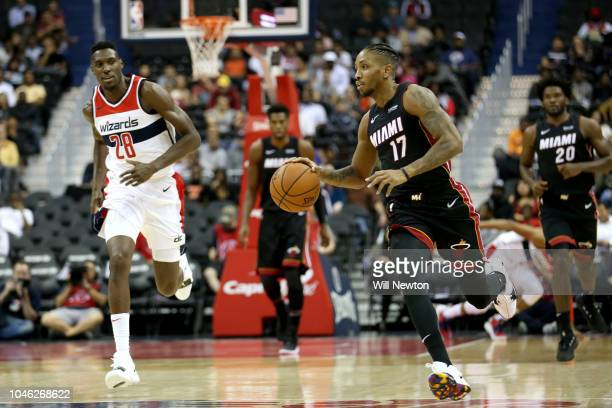 Rodney McGruder of the Miami Heat dribbles the ball in front of Ian Mahinmi of the Washington Wizards during the first half of a preseason NBA game...