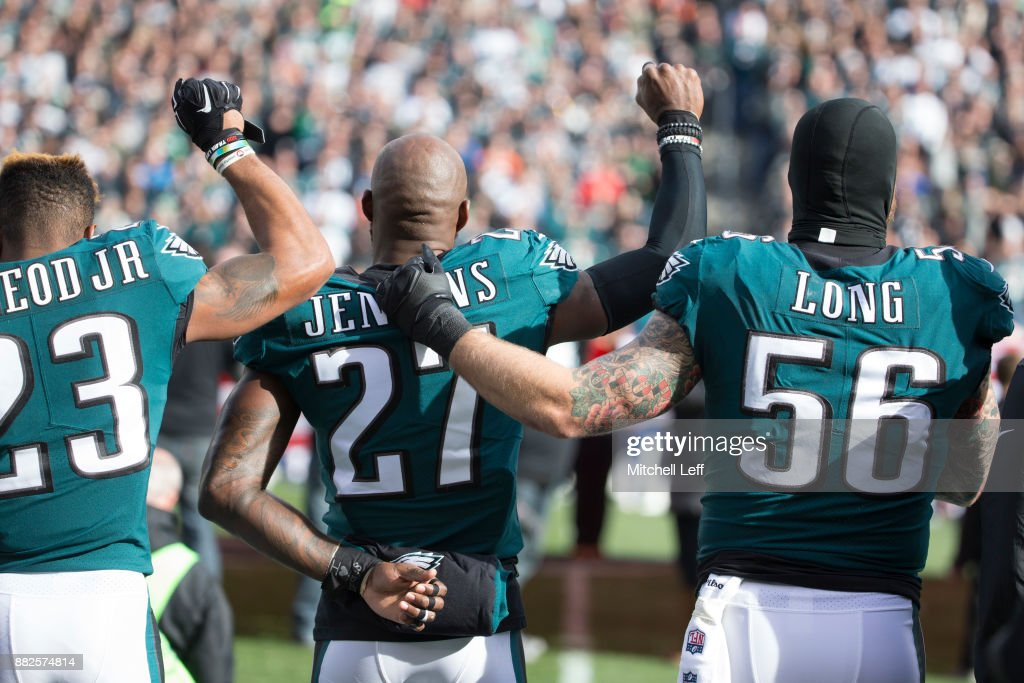 Rodney McLeod #23 and Malcolm Jenkins #27 of the Philadelphia Eagles raise their fists as teammate Chris Long #56 stands alongside them during the national anthem prior to the game against the Chicago Bears at Lincoln Financial Field on November 26, 2017 in Philadelphia, Pennsylvania.