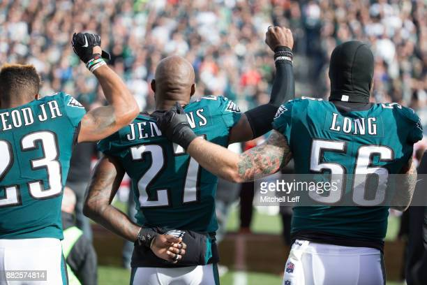 Rodney McLeod and Malcolm Jenkins of the Philadelphia Eagles raise their fists as teammate Chris Long stands alongside them during the national...