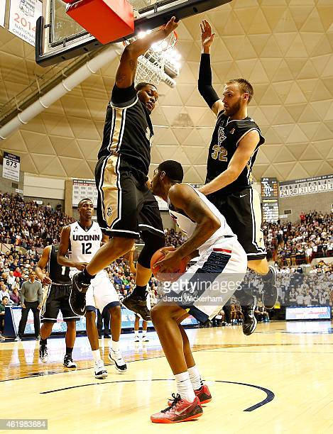 Rodney Purvis of the Connecticut Huskies is defended underneath the basket by Justin McBride and Kasey Wilson of the Central Florida Knights in the...