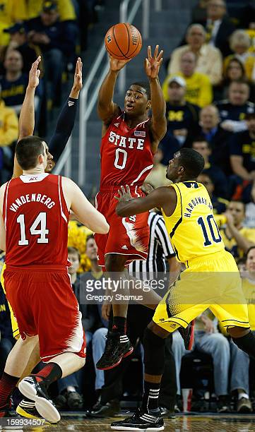 Rodney Purvis of the North Carolina State Wolfpack tries to get a first half pass to Jordan Vandenberg around Tim Hardaway Jr #10 of the Michigan...