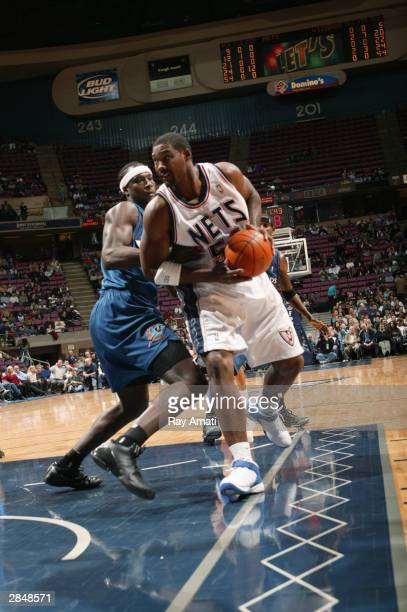Rodney Rogers of the New Jersey Nets is defended by Kwame Brown of the Washington Wizards during the game at Continental Airlines Arena on December...