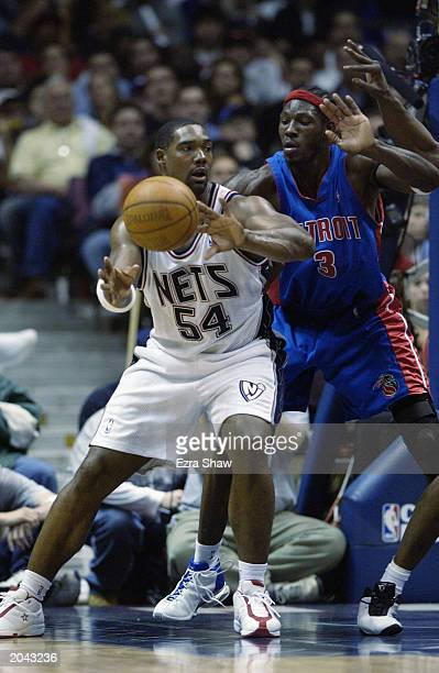 Rodney Rogers of the New Jersey Nets passes the ball while defended by Ben Wallace of the Detroit Pistons in Game Four of the Eastern Conference...