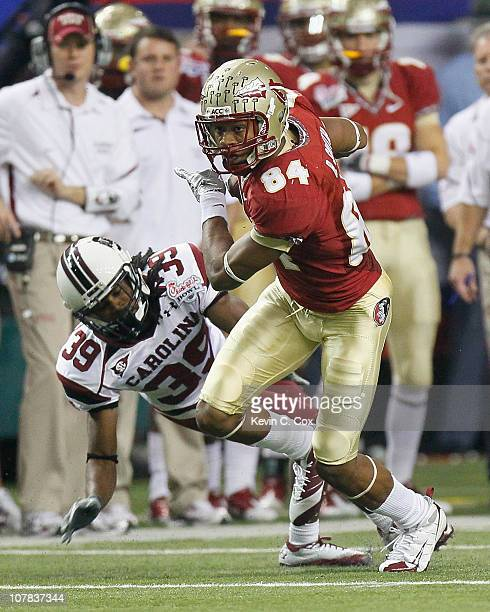 Rodney Smith of the Florida State Seminoles breaks a tackle by Marty Markett of the South Carolina Gamecocks during the 2010 ChickfilA Bowl at...
