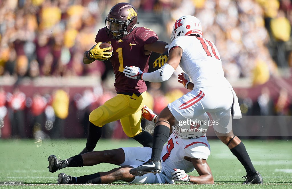 Rodney Smith #1 of the Minnesota Golden Gophers carries the ball against Saquan Hampton #9 and Isaiah Wharton #11 of the Rutgers Scarlet Knights during the fourth quarter of the game on October 22, 2016 at TCF Bank Stadium in Minneapolis, Minnesota. The Golden Gophers defeated the Scarlet Knights 34-32.