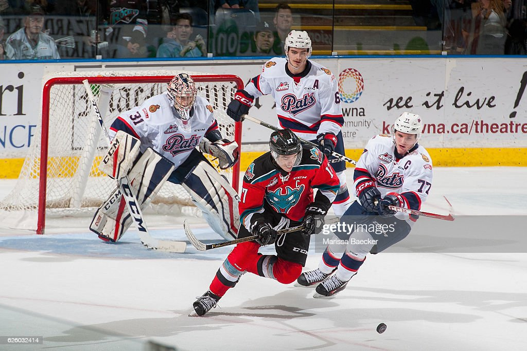 Rodney Southam #17 of the Kelowna Rockets is stick checked by Adam Brooks #77 in front of the net of Tyler Brown #31 of the Regina Pats during overtime on November 26, 2016 at Prospera Place in Kelowna, British Columbia, Canada.