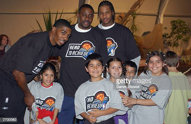 Rodney White Community Ambassador Micheal Ray Richardson and Carmelo Anthony of the Denver Nuggets pose for a photo with children as part of the NBA...