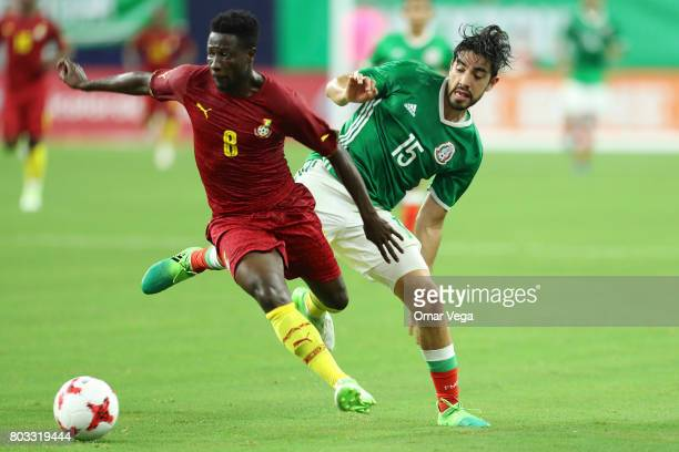 Rodofo Pizarro of Mexico fights for the ball with Ebenezer Ofori of Ghana during the friendly match between Mexico and Ghana at NRG Stadium on June...