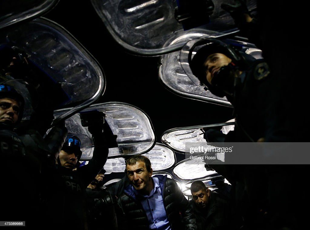 Rodolfo Arruabarena coach of Boca Juniors walks out the field protected by the police after a second leg match between Boca Juniors and River Plate was suspended as part of round of sixteen of Copa Bridgestone Libertadores 2015 at Alberto J. Armando Stadium on May 14, 2015 in Buenos Aires, Argentina.