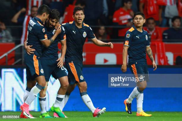 Rodolfo Pizarro of Chivas celebrates with teammates after scoring his team's first goal during the semifinals first leg match between Toluca and...