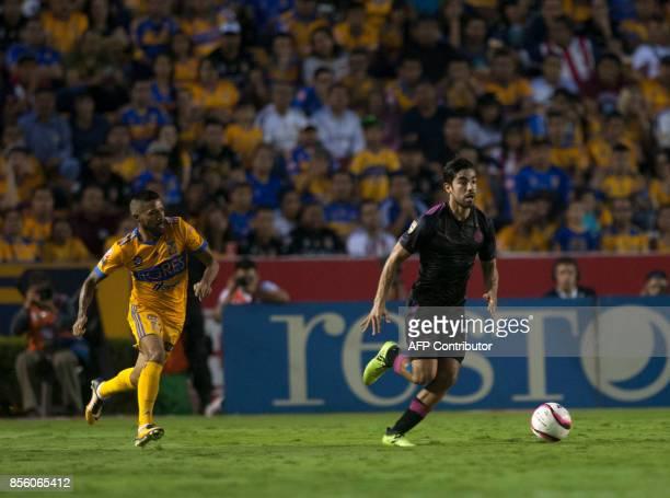 Rodolfo Pizarro of Chivas drives the ball past Javier Aquino of Tigres during their Mexican Apertura football tournament match at the Universitario...