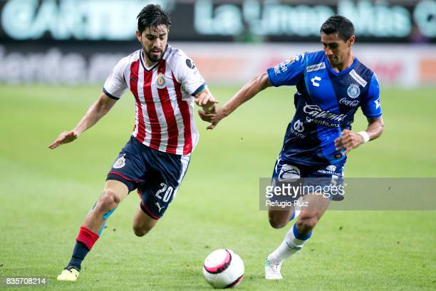 Rodolfo Pizarro of Chivas fights for the ball with Patricio Araujo of Puebla during the fifth round match between Chivas and Puebla as part of the...
