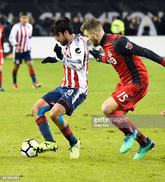 Rodolfo Pizarro of Chivas Guadalajara battles for the ball with Eriq Zavaleta of Toronto FC during the CONCACAF Champions League Final Leg 1 on April...