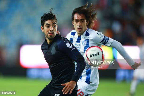 Rodolfo Pizarro of Chivas struggles for the ball with Jose Martinez of Pachuca during the 8th round match between Pachuca and Chivas as part of the...
