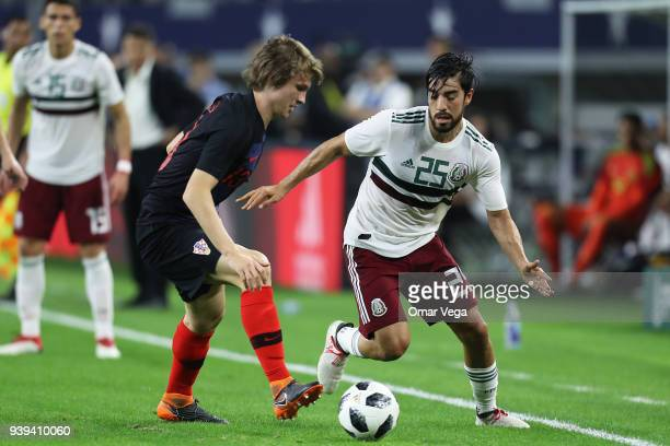 Rodolfo Pizarro of Mexico and Ante Revic of Croatia fight for the ball during the international friendly match between Mexico and Croatia at ATT...