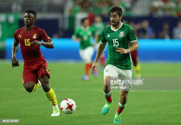 Rodolfo Pizarro of Mexico drives the ball followed by Rashid Sumalia of Ghana during the friendly match between Mexico and Ghana at NRG Stadium on...