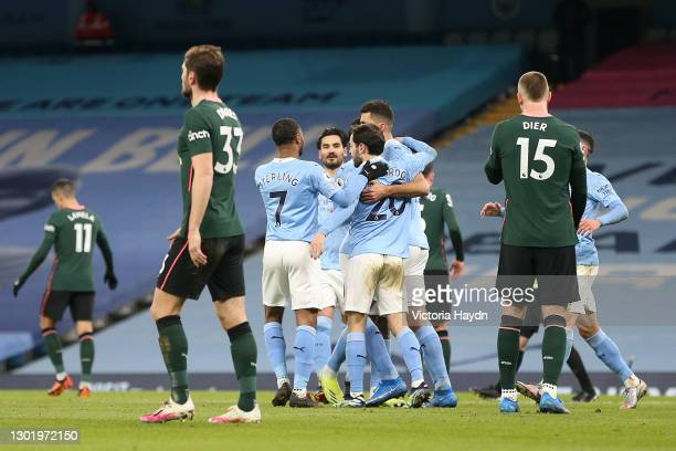 Rodri of Manchester City celebrates with teammates after scoring their team's first goal from a penalty during the Premier League match between...