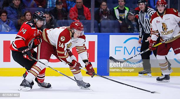 Rodrigo Abols of the Acadie-Bathurst Titan and Olivier Garneau of the Quebec Remparts battle for the puck during their QMJHL hockey game at the...