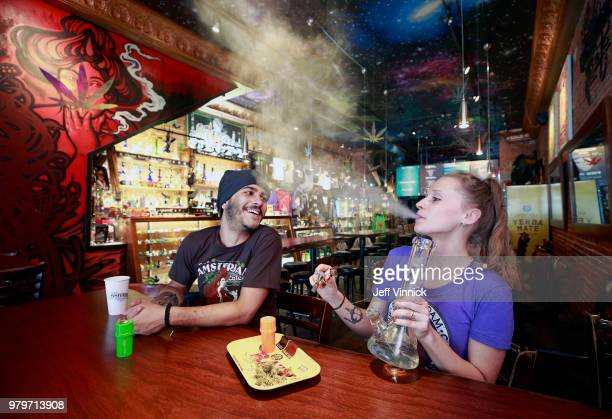 Rodrigo Acevedo Casino looks on as Anna Bolechowska smokes marijuana with a bong at the New Amsterdam Cafe June 20 2018 in Vancouver British Columbia...