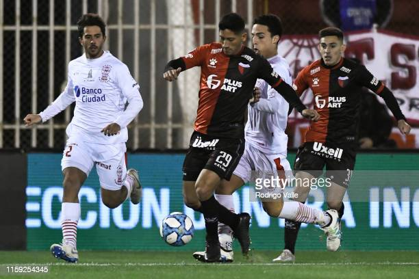 Rodrigo Aliendro of Colon drives the ball under pressure of Gonzalo Bettini and Lorenzo Faravelli of Huracan during a match between Huracán and...