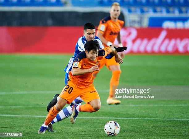 Rodrigo Battaglia of Deportivo Alaves duels for the ball with Kangin Lee of Valencia CF during the LaLiga Santander match between Alaves and Valencia...