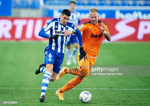 Rodrigo Battaglia of Deportivo Alaves duels for the ball with Uros Racic of Valencia CF during the LaLiga Santander match between Alaves and Valencia...
