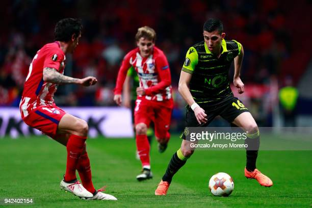 Rodrigo Battaglia of Sporting CP competes for the ball with Stefan Savic of Atletico de Madrid and his teammate Antoine Griezmann during the UEFA...
