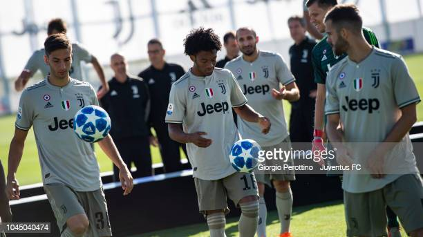 Rodrigo Bentancur and Juan Cuadrado play with the ball during the Juventus Official Team Photo at JTC on October 3 2018 in Turin Italy