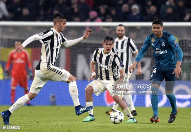 Rodrigo Bentancur and Paulo Dybala of Juventus compete for the ball with Casemiro of Real Madrid during the UEFA Champions League Quarter Final Leg...