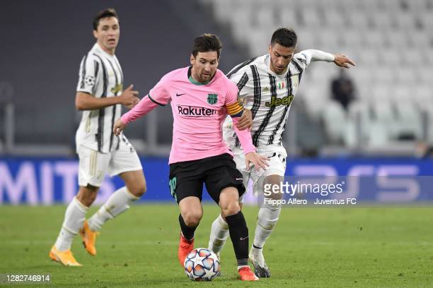 Rodrigo Bentancur of Juventus competes for the ball with Lionel Messi of FC Barcelona during the UEFA Champions League Group G stage match between...