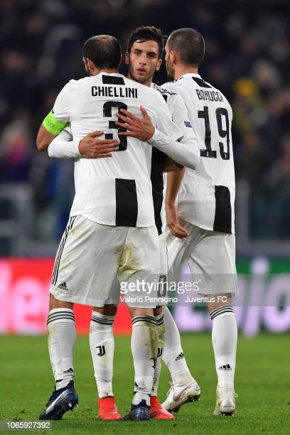 Rodrigo Bentancur of Juventus hugs his teammates Giorgio Chiellini and Leonardo Bonucci and celebrate the victory at the end of the Group H match of...
