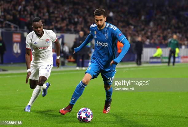 Rodrigo Bentancur of Juventus is challenged by Maxwel Cornet of Olympique Lyon during the UEFA Champions League round of 16 first leg match between...