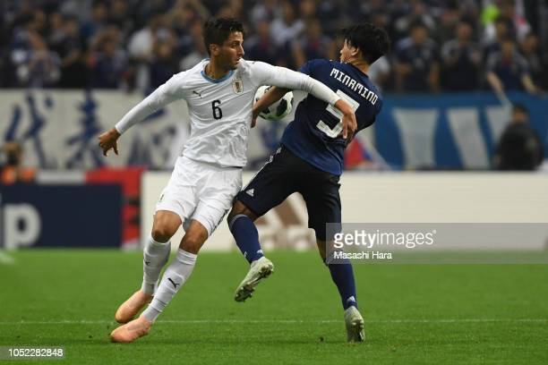 Rodrigo Bentancur of Uruguay and Takumi Minamino of Japan compete for the ball during the international friendly match between Japan and Uruguay at...
