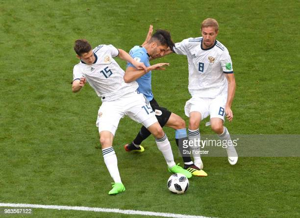 Rodrigo Bentancur of Uruguay challenge for the ball with Alexey Miranchuk and Iury Gazinsky during the 2018 FIFA World Cup Russia group A match...