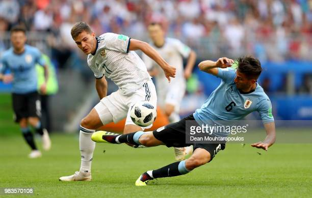 Rodrigo Bentancur of Uruguay is tackled by Roman Zobnin of Russia during the 2018 FIFA World Cup Russia group A match between Uruguay and Russia at...