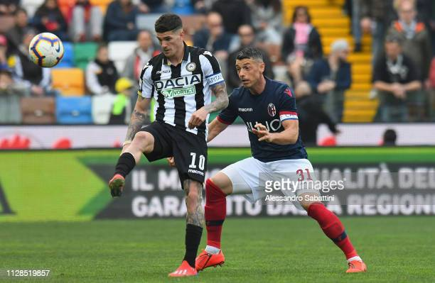 Rodrigo De Paul of Udinese Calcio competes for the ball with Blerim Dzemaili of Bologna FC during the Serie A match between Udinese and Bologna FC at...