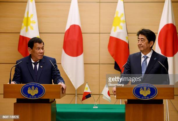 Rodrigo Duterte the Philippines' president left and Shinzo Abe Japan's prime minister stand at podiums during a joint news conference in Tokyo Japan...