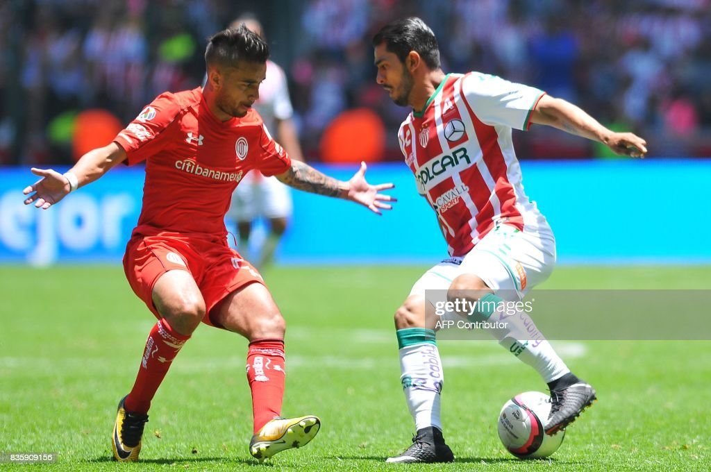Rodrigo Gomez (L) of Toluca marks Miguel Ponce of Necaxa during their Mexican Apertura football tournament match at the Nemesio Diez stadium in Toluca, Mexico, on August 20, 2017. /