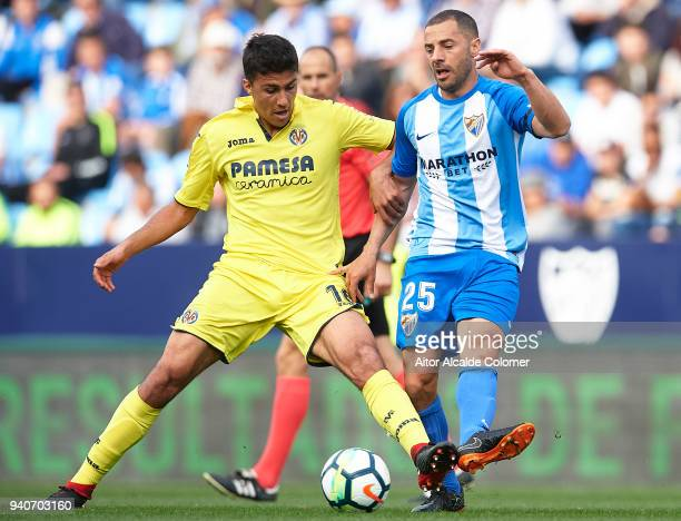 Rodrigo Hernandez of Villarreal CF competes for the ball with Medhi Lacen of Malaga CF during the La Liga match between Malaga and Villarreal at...