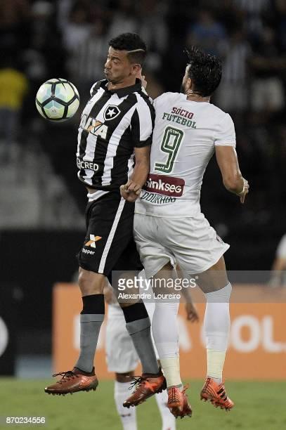 Rodrigo Lindoso of Botafogo battles for the ball with Henrique Dourado of Fluminense during the match between Botafogo and Fluminense as part of...