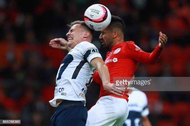 Rodrigo Lopez of Toluca jumps for a header with Abraham Gonzalez of Pumas during the 11th round match between Toluca and Pumas UNAM as part of the...