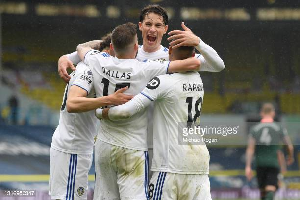 Rodrigo of Leeds United celebrates with Stuart Dallas and Raphinha after scoring their side's third goal during the Premier League match between...