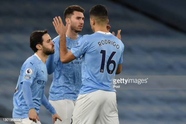 Rodrigo of Manchester City interacts with with team mates Bernardo Silva and Aymeric Laporte prior to the Premier League match between Manchester...