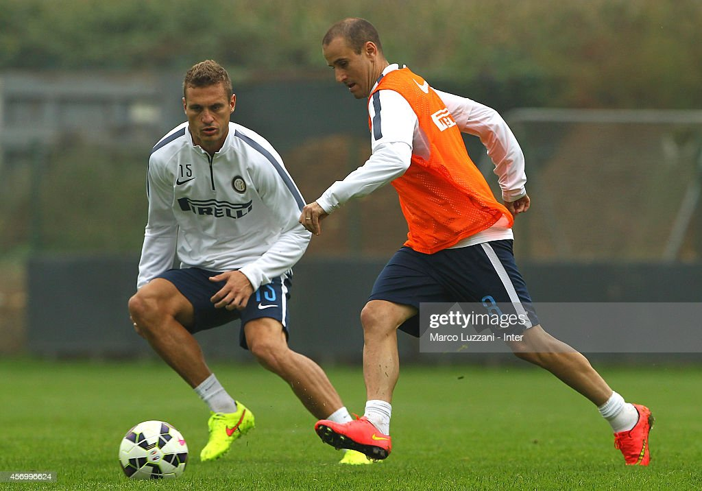 Rodrigo Palacio (R) competes with Nemanja Vidic (L) during FC Internazionale training session at the club's training ground on October 10, 2014 in Appiano Gentile Como, Italy.
