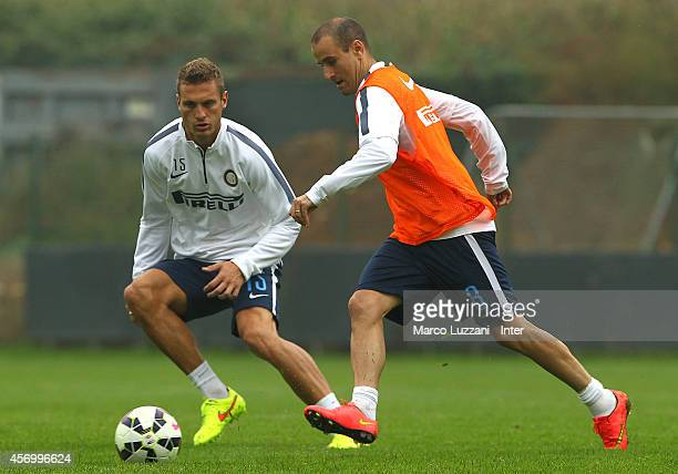 Rodrigo Palacio competes with Nemanja Vidic during FC Internazionale training session at the club's training ground on October 10, 2014 in Appiano...