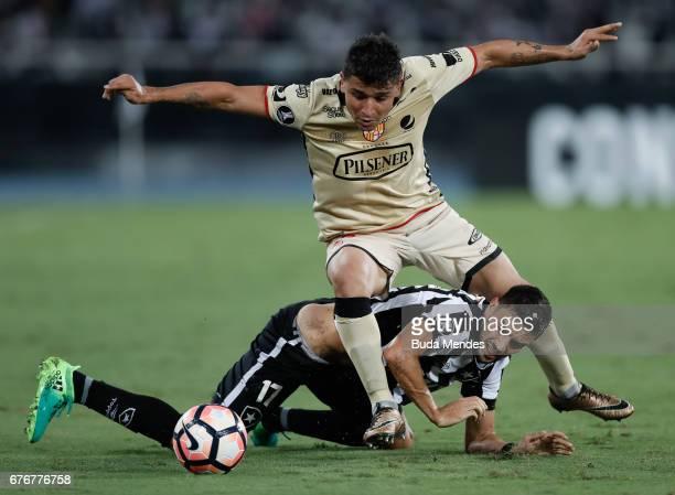 Rodrigo Pimpao of Botafogo struggles for the ball with Mario Pineida of Barcelona de Guayaquil during a match between Botafogo and Barcelona de...