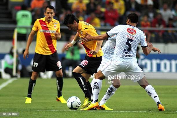 Rodrigo Salinas and Hector Mancilla of Morelia vie for the ball with Jose Maria Basanta of Monterrey during their Mexican Apertura tournament...