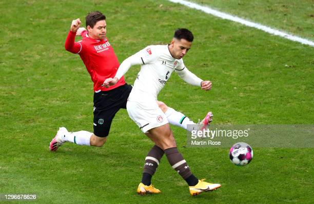 Rodrigo Zalazar of FC St. Pauli is challenged by Dominik Kaiser of Hannover 96 as he scores his team's first goal during the Second Bundesliga match...