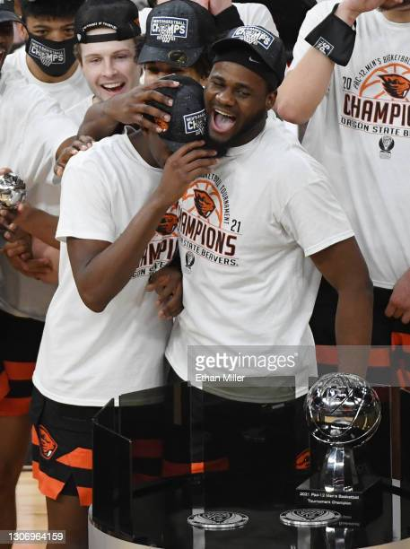 Rodrigue Andela of the Oregon State Beavers hugs Warith Alatishe after he was announced as the winner of the most outstanding player award following...