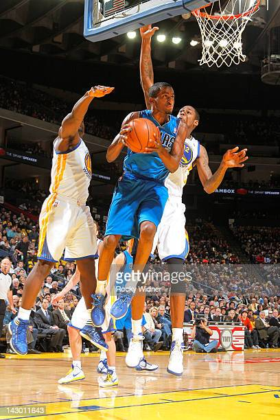 Rodrigue Beaubois of the Dallas Mavericks attempts a tough shot against Mickell Gladness of the Golden State Warriors on April 12, 2012 at Oracle...